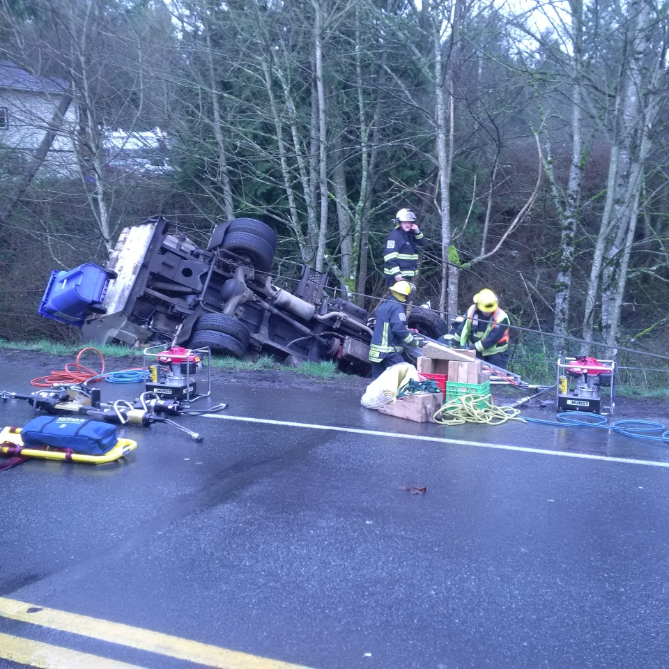 Driver rescued after garbage truck rolls over in Sooke, hangs off ...