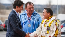 Justin Trudeau, left, greeted by Tsuu T'ina Chief