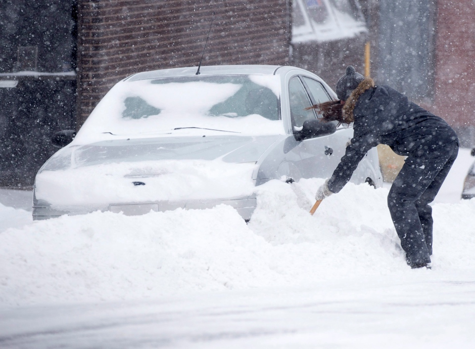 A motorist digs out a car in Halifax on Saturday, March 5, 2016. Heavy snow and winds are buffeting parts of Nova Scotia with zero visibility and poor travel conditions. (Andrew Vaughan/THE CANADIAN PRESS)