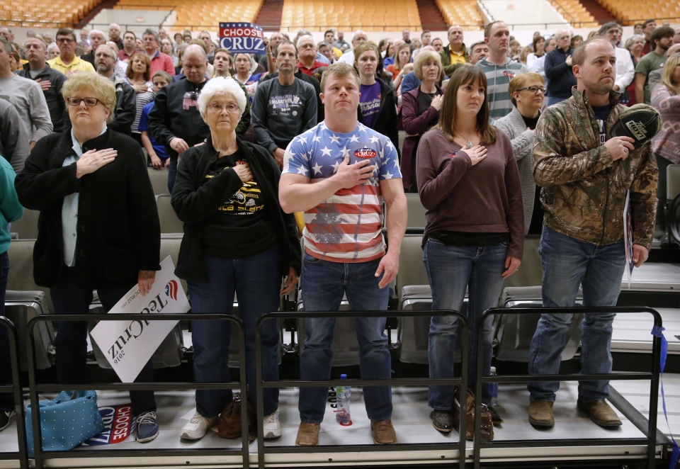 Wichita, Kan., residents prepare for the pledge allegiance at a caucus site, Saturday, March 5, 2016, in Wichita. (AP/Charles Rex Arbogast)