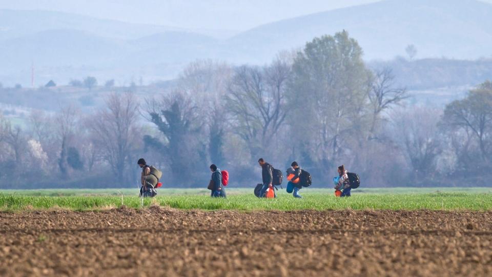 Migrants walk in a field on a foggy morning near the northern Greek border station of Idomeni, Sunday, March 6, 2016. (AP / Vadim Ghirda)