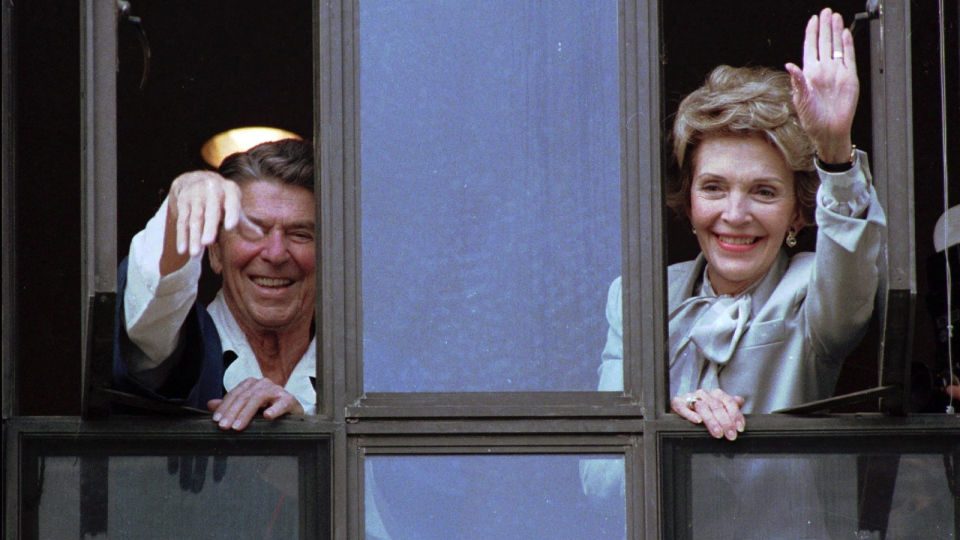 In this July 18, 1985, file photo, President Ronald Reagan and his wife, Nancy, wave from windows of his hospital room at the Navy Medical Center in Bethesda, Md. (AP / Scott Stewart, File)