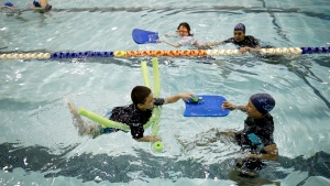 Young swimmers and their teachers swim in a pool during a swim lesson in the Bronx borough of New York, Wednesday, April 15, 2015. They are in swim swim swim I SAY, one of 65 programs around the country to receive grants from the nonprofit Autism Speaks to provide the personal attention and patience if often takes to help children on the autism spectrum learn to swim. (AP / Seth Wenig)