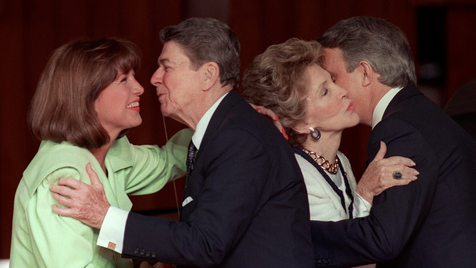 Mila Mulroney (left) gets a kiss from then U.S. President Ronald Reagan as his wife Nancy gets a kiss from Prime Minister Brian Mulroney (right) at the official welcoming ceremony for the economic summit in Toronto June 19, 1988. (CP ARCHIVE PHOTO/Ron Poling)