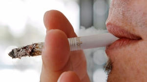 A man smokes a cigarette in Hialeah, Fla., Feb.7, 2011. THE CANADIAN PRESS/AP Photo/Alan Diaz