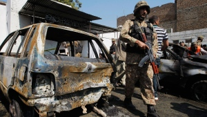 A Pakistani soldier walks past damaged vehicles at the site of a deadly suicide bombing in Charsadda, Pakistan, Monday, March 7, 2016 (AP / Mohammad Sajjad).
