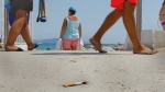n this Aug. 2, 2011 photo, tourists and a cigarette butt share the sand at La Ciotat beach near Marseille, southern France. (Jacques Brinon / AP Photo)