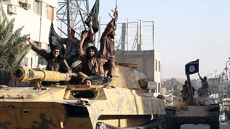 In this undated file image posted by the Raqqa Media Center, in Islamic State group-held territory, on Monday, June 30, 2014, fighters from the Islamic State group ride tanks during a parade in Raqqa, Syria. (Raqqa Media Center via AP)