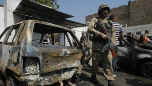 A Pakistani soldier walks past damaged vehicles at the site of a deadly suicide bombing in Charsadda on Pakistan, Monday, March 7, 2016. (AP / Mohammad Sajjad)