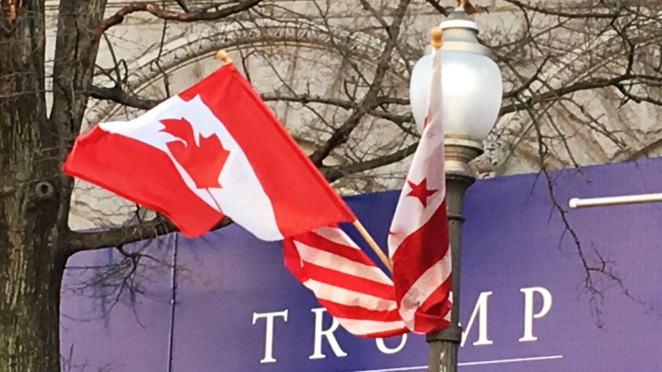 Canadian and American flags fly on Washington's Pennsylvania Avenue in front of a Trump International Hotel sign on Monday, March 7, 2016. (THE CANADIAN PRESS/Alexander Panetta)
