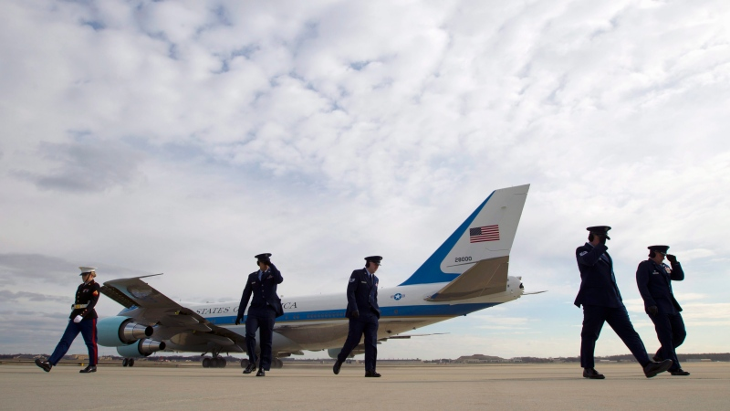 Military personnel hold their hats as Air Force One, with President Barack Obama aboard, departs from Andrews Air Force Base, Md., Wednesday, Feb. 10, 2016. ( AP / Jose Luis Magana)