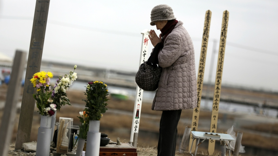 A woman prays for tsunami victims at a makeshift shrine in a neighborhood devastated by the March 11, 2011 earthquake and tsunami on top of Hiyoriyama in Natori, Miyagi Prefecture, northeastern Japan on Saturday, March 5, 2016. (AP / Eugene Hoshiko)