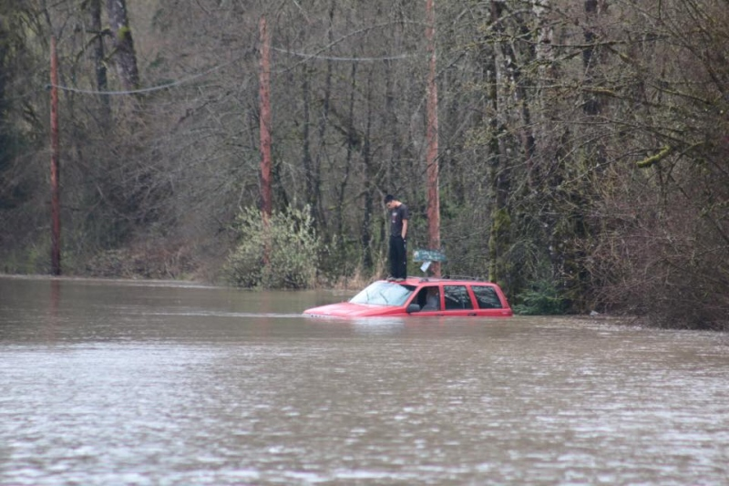 A man is seen standing on the roof of his car after getting trapped by floodwater on Cowichan Bay Road, March 10, 2016. (Cowichan Valley Citizen/Kevin Rothbaeur)