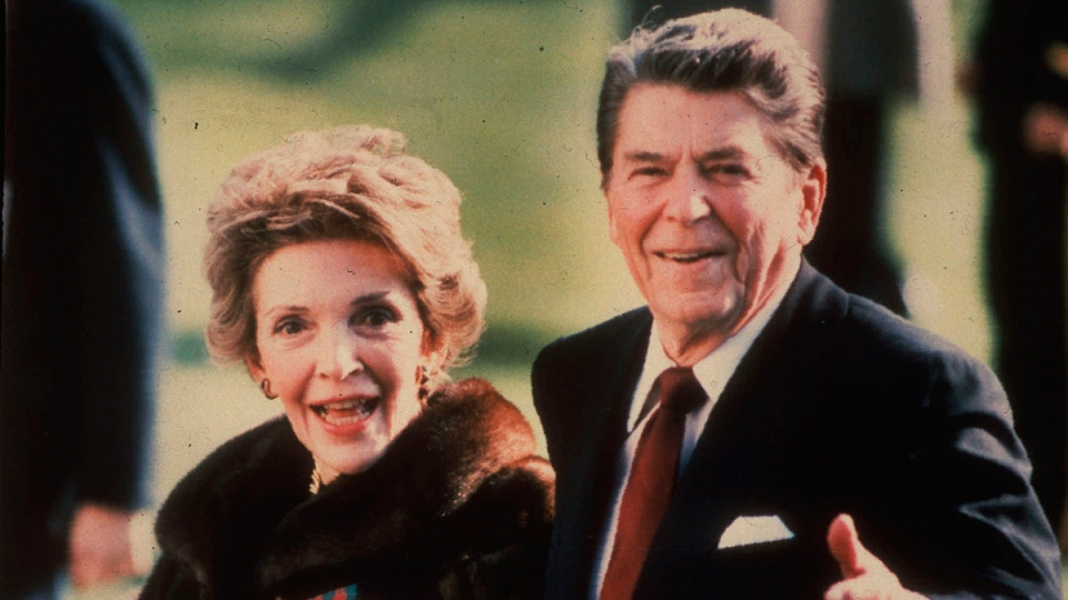 This December 1986 photo shows first lady Nancy Reagan holding the Reagans' pet Rex, a King Charles spaniel, as she and President Reagan walk on the White House South lawn. (AP / Dennis Cook)