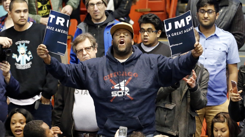 A protester holds up a ripped campaign sign for Republican presidential candidate Donald Trump at the University of Illinois-Chicago, on Friday, March 11, 2016. (AP Photo/Charles Rex Arbogast)