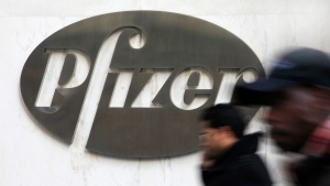 In this file photo from Jan. 31, 2011, people walk past the Pfizer logo at the drug company's world headquarters in New York. (AP/Mark Lennihan)