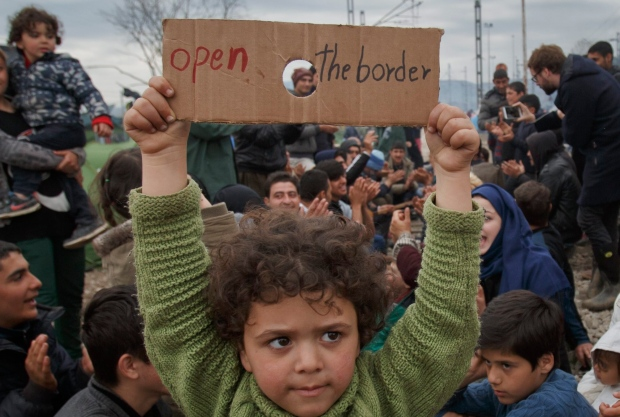 Child holds sign during migrant protests