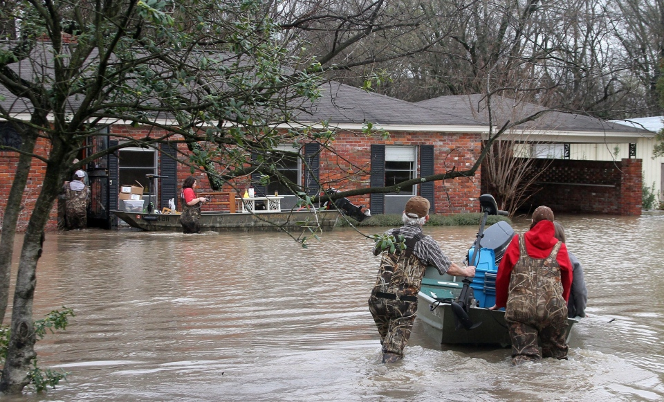Volunteers return to a flooded house in Clarksdale, Miss., Friday, March 11, 2016, to assist the owners retrieve personal items as flood waters continued to rise following another morning of rain. (Troy Catchings/The Clarksdale Press Register, via AP)
