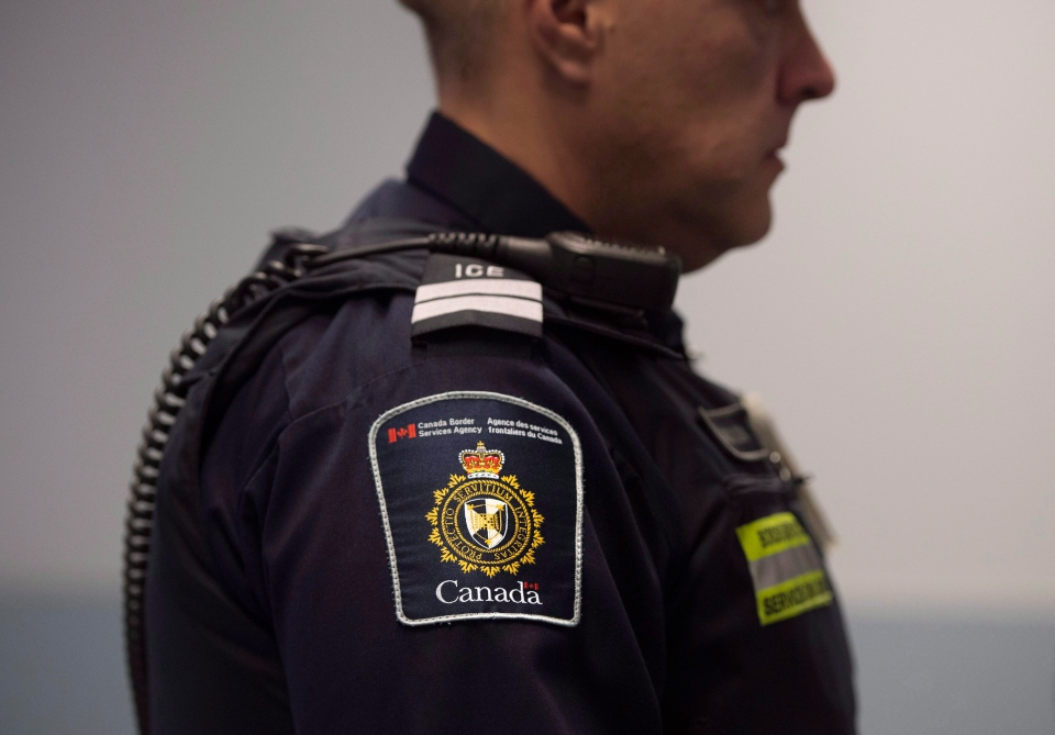 A Canadian Border Services agent stands watch at Pearson International Airport in Toronto, Ont. on Tuesday, December 8, 2015. (Darren Calabrese/THE CANADIAN PRESS)