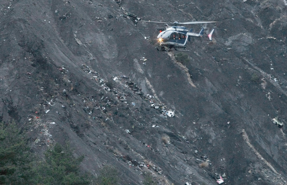 In this March 24, 2015 file picture a recue helicopter flies over debris of the Germanwings passenger jet, scattered on the mountain side, near Seyne les Alpes, French Alps and killing all 150 people on board.(AP/Claude Paris)