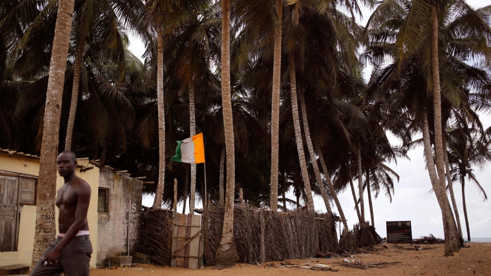 In this file photo taken on Tuesday, Oct. 27, 2015, a man, passes a home stead, with an Ivory Coast national flag, center, seen at a fishing village renowned as a tourist hot spot visited by French and other tourist yearly in Grand Bassam, Ivory Coast.  (AP / Schalk van Zuydam, File)