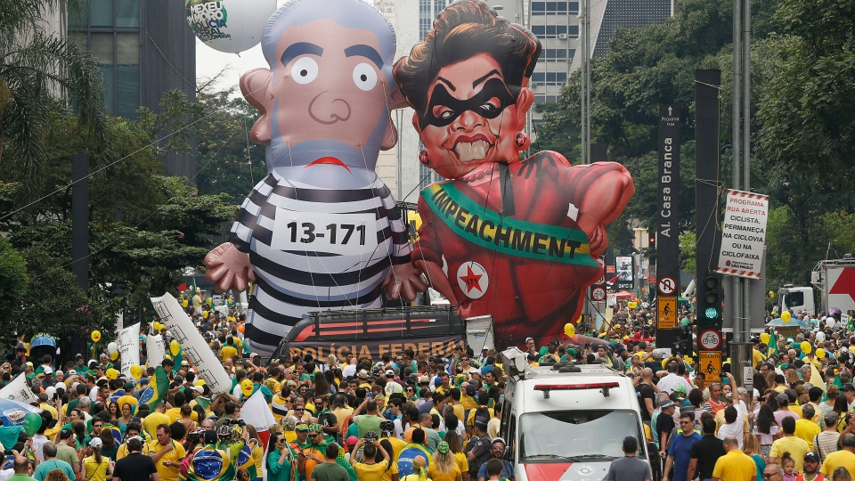 """Demonstrators parade large inflatable dolls depicting Brazil's former President Luiz Inacio Lula da Silva in prison garb and current President Dilma Rousseff dressed as a thief, with a presidential sash that reads """"Impeachment,"""" in Sao Paulo, Brazil, Sunday, March 13, 2016. (AP /Andre Penner)"""