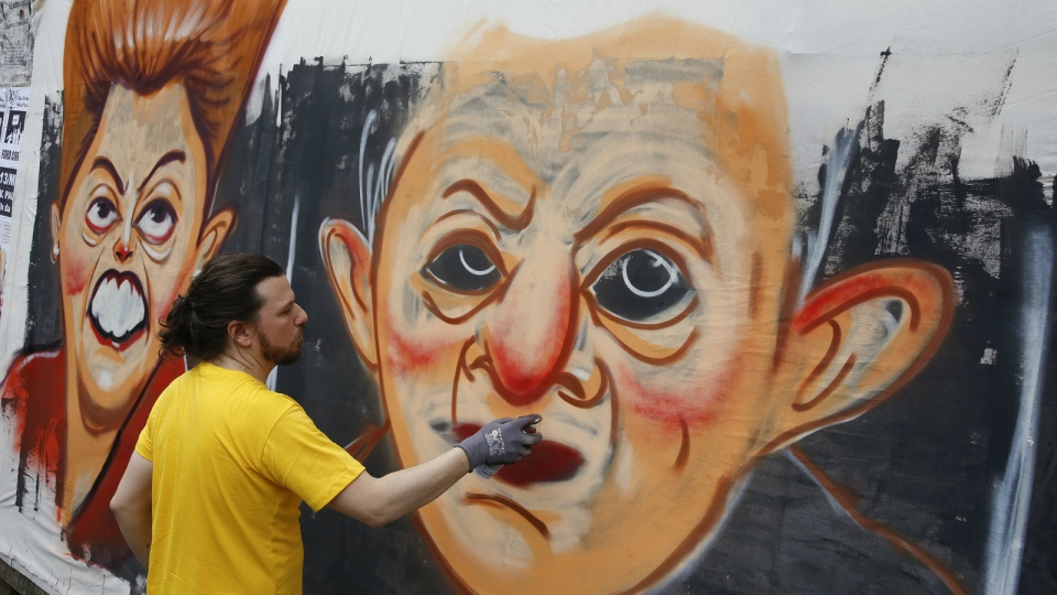 A street artist spray paints caricatures of Brazil's former President Luiz Inacio Lula da Silva, center, and current President Dilma Rousseff during a protest demanding her impeachment in Sao Paulo, Brazil, Sunday, March 13, 2016. (AP / Andre Penner)