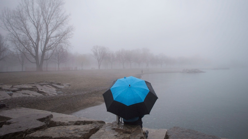 A man sits on the shore of Lake Ontario on a misty day on the lake shore in Toronto, on Thursday, March 10 2016. THE CANADIAN PRESS/Chris Young