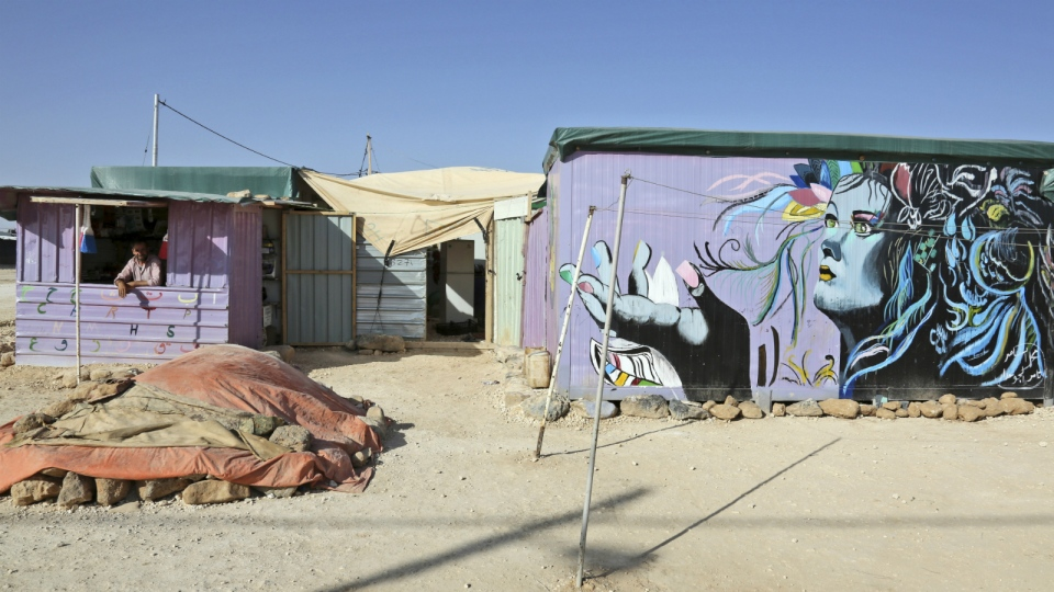 A Syrian refugee man, left, stands inside his grocery store painted by refugee artists, in the Zaatari Refugee Camp, near Mafraq, Jordan on Monday, March 7, 2016. (AP / Raad Adayleh)