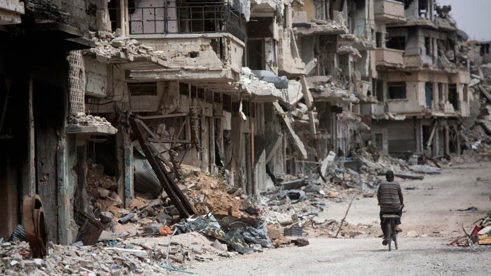 A man rides a bicycle through a devastated part of Homs, Syria, on June 5, 2014. (Dusan Vranic / AP)