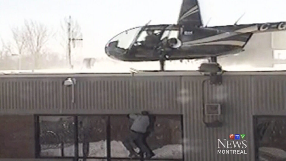 A prisoner climbs up to a hijacked helicopter in this video of a prison break in Saint-Jerome, Que., on March 17, 2013.