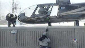 A prisoner climbs up to meet an accomplice in front of a a hijacked helicopter in this video of a prison break in Saint-Jerome, Que., on March 17, 2013.