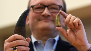 Hans-Dieter Sues, chair of the Department of Paleobiology at the Smithsonian's National Museum of Natural History, holds up a tooth of a new dinosaur, Timurlengia euotica, right, in comparison to the tooth of a Tyrannosaurus rex, left, following a news conference in Washington, Monday, March 14, 2016. (AP / Susan Walsh)