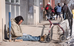 Lefty, who is homeless, sits on a sidewalk in downtown Thunder Bay, Friday, March 4, 2016. He joins other homeless people at Shelter House for meals and a bed. (Paul Chiasson / THE CANADIAN PRESS)