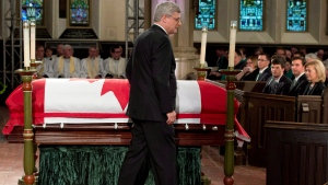 Prime Minister Stephen Harper walks past the casket of Jim Flaherty during the during the former finance minister's state funeral in Toronto, on Wednesday, April 16, 2014. (THE CANADIAN PRESS/Frank Gunn)