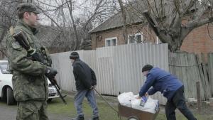 Residents carry humanitarian aid distribution by EU humanitarian program as Ukrainian soldier guard the area in Semonovka, Eastern Ukraine on Thursday, March 17, 2016. (AP / Efrem Lukatsky)