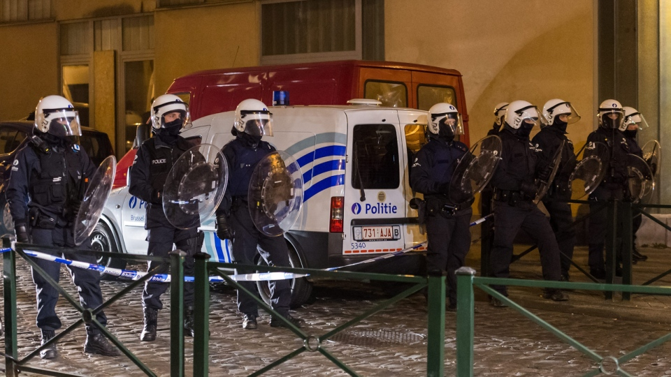 Police officers secure a street during a raid in the Molenbeek neighborhood of Brussels, Belgium, Friday March 18, 2016. (AP / Geert Vanden Wijngaert)