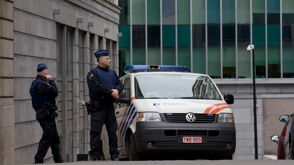 Security forces guard the federal police headquarters, rear, where captured fugitive Salah Abdeslam appeared before a judge in Brussels, Belgium, Saturday, March 19, 2016. (AP / Peter Dejong)