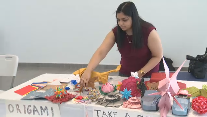 Anita Raj arranges origami on a table. The McGill medical student is part of a group that organized Journeys Through Health Care, a display of artwork created by 21 patients, caregivers, and healthcare providers at the MUHC.