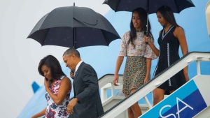 Former U.S. president Barack Obama, second from left, arrives with former first lady Michelle Obama, left, and their daughters Sasha, right, and Malia, as they exit Air Force One at the airport in Havana, Cuba, Sunday, March 20, 2016. (AP / Pablo Martinez Monsivais).