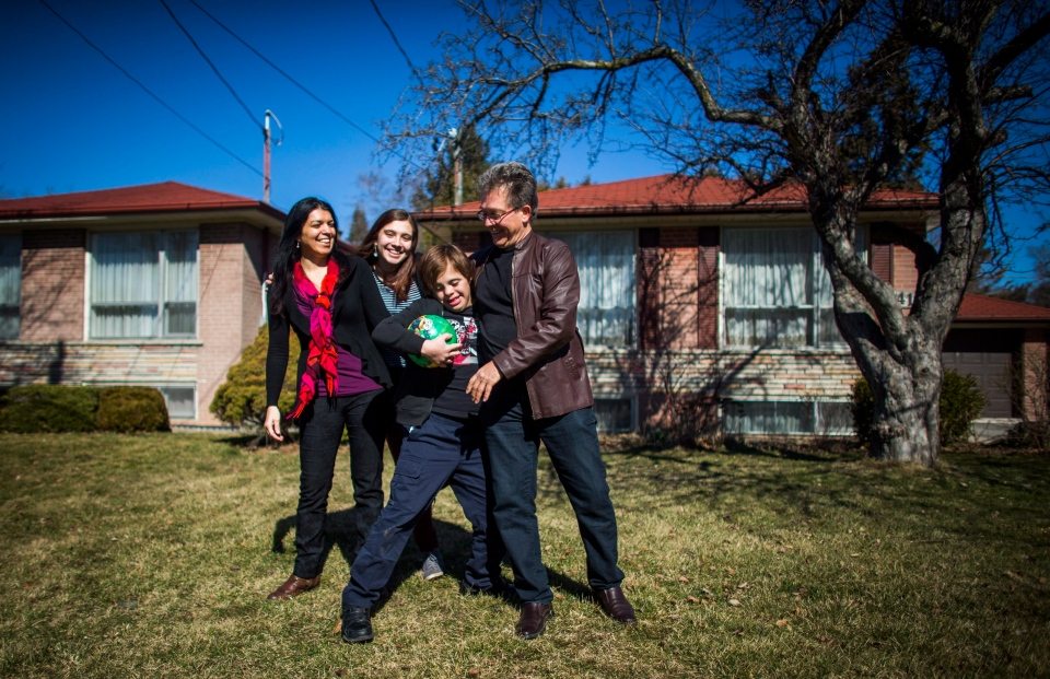 Nico Montoya, a 13-year-old boy with Down syndrome, plays soccer with his home with his father Felipe, right, his sister Tania, second left, and his mother Alejandra Garcia, left, at their home in Richmond Hill, Ont., on Saturday, March 19, 2016. (THE CANADIAN PRESS/Mark Blinch)