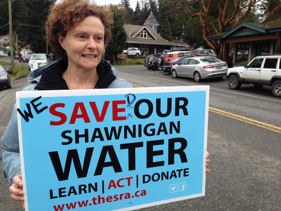 A Shawnigan Lake resident holds up a sign reading 'We saved our Shawnigan water,' after the BC Supreme Court ruled in favour of residents against a contaminated soil facility above the town's watershed. March 21, 2016. (CTV Vancouver Island)