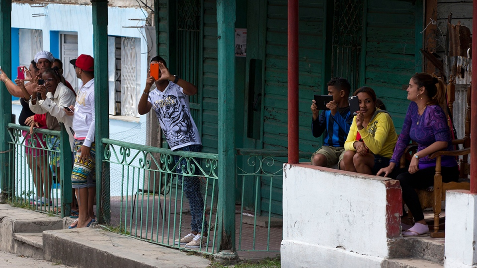 Local residents capture images with their mobile devices, from their front porches as the convoy carrying U.S. First Lady Michelle Obama arrives at Hemmingway House, in the San Francisco de Paula district of Havana, Cuba, Monday, March 21, 2016. (AP / Rebecca Blackwell)
