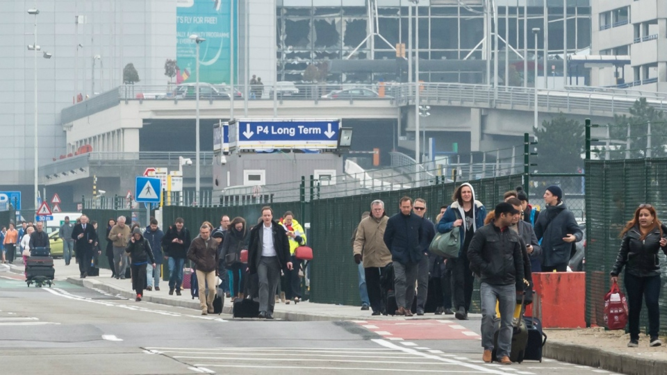 People walk away from Brussels airport after explosions rocked the facility in Brussels, Belgium Tuesday March 22, 2016. (AP / Geert Vanden Wijngaert)