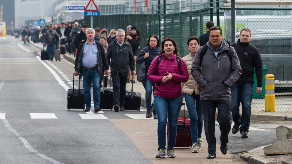 People walk away from Brussels airport after explosions on March 22, 2016. (Geert Vanden Wijngaert / AP)