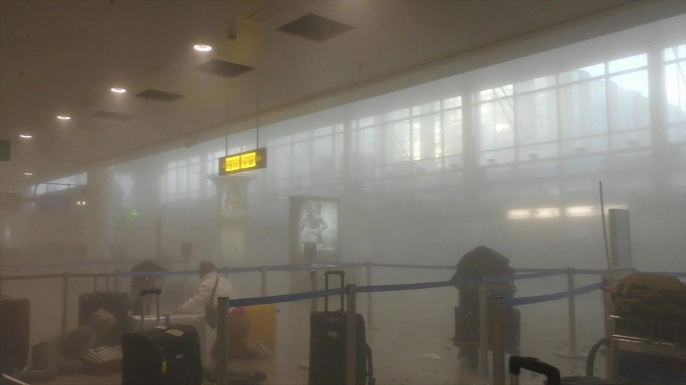 An unidentified traveller gets to his feet in a smoke-filled terminal at Brussels Airport, in Brussels after explosions Tuesday, March 22, 2016. (Ralph Usbeck via AP)