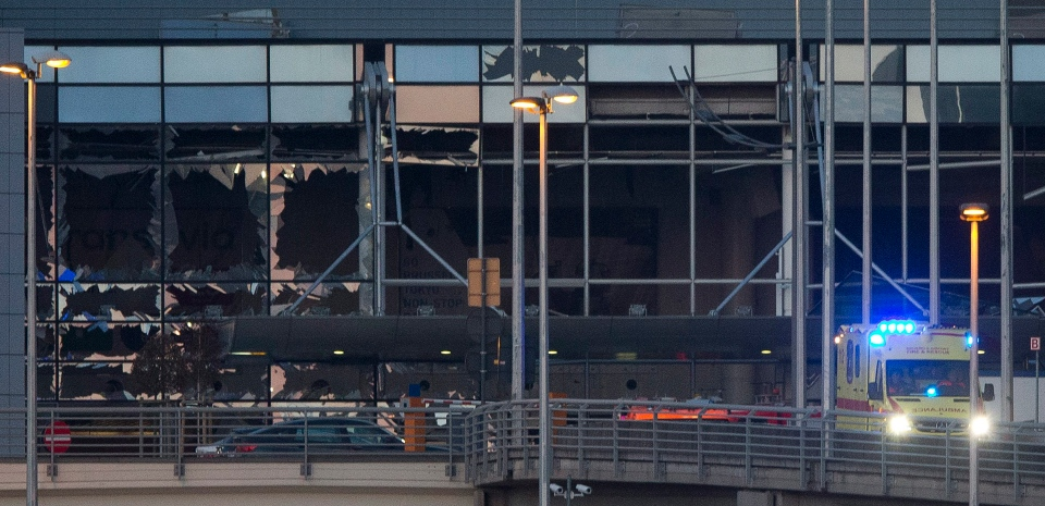 The blown out facade of the terminal is seen as an ambulance leaves Zaventem airport, one of the sites of two deadly attacks in Brussels, Belgium on March 22, 2016. (Peter Dejong / AP Photo)