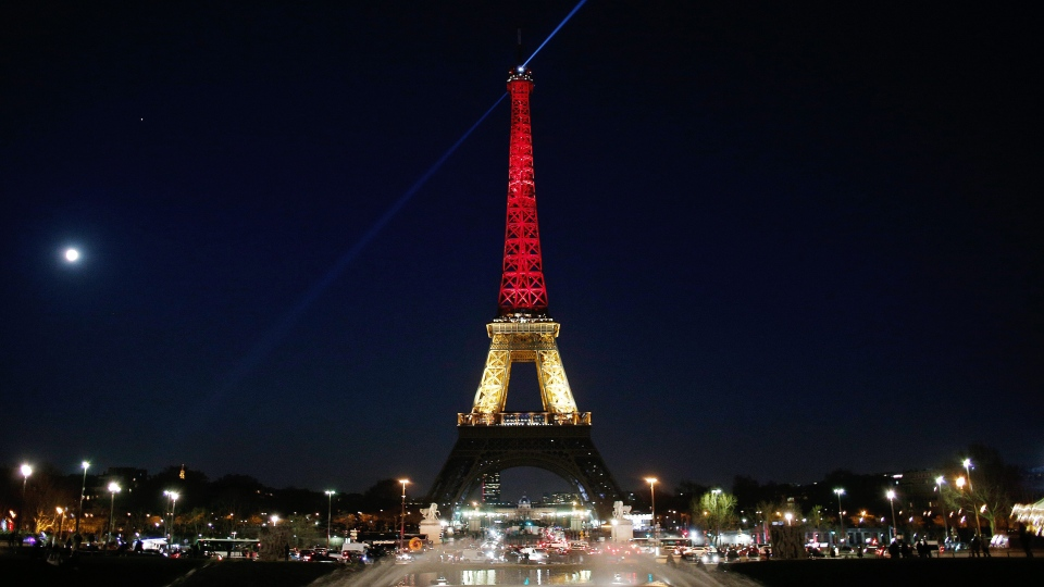 The Eiffel Tower is illuminated with the Belgium national colors black, yellow and red in honor of the victims of the today's attacks at the airport and the metro station in Brussels, in Paris, on Tuesday, March 22, 2016.  (AP Photo/Thibault Camus)