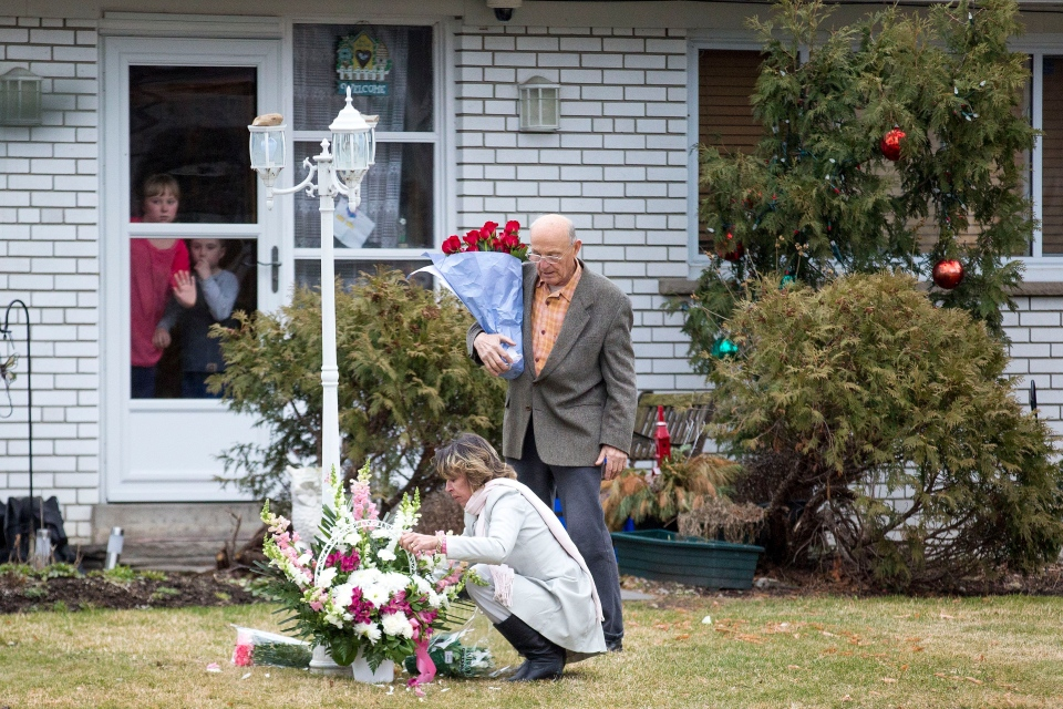 Stephanie and Doug Ford watch as their mother Renata and neighbour Zdravko Gagro arrange flowers left at the family home in Toronto following the death of Coun. Rob Ford on Tuesday, March 22, 2016. (The Toronto Star / Carlos Osorio)
