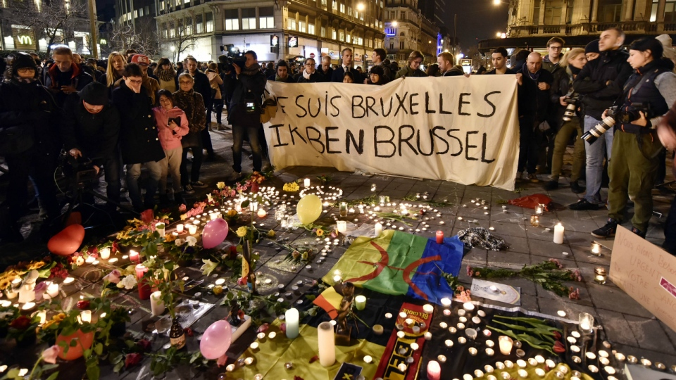 People holding a banner reading 'I am Brussels' behind flowers and candles to mourn for the victims at Place de la Bourse in the centre of Brussels, Tuesday, March 22, 2016. (AP / Martin Meissner)